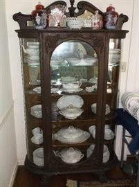 Ornate oak curved glass china cabinet w/Limoges china including great serving pieces