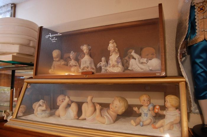 Store counter display cases, piano babies, German pin cushion toppers
