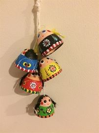 These are small painted terra-cotta bells hanging on a kitchen wall.