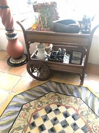 Mackenzie Child's 'Campaign Courtly' rattan serving cart with area rug.