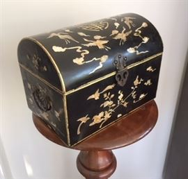 "Black lacquer box with mother of pearl inlays with stylized bird, cloud, and flower motifs flanking a central ""shou"" or longevity motif. Date unknown; probably 20th century."