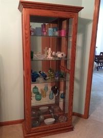 Oak Curio Cabinet with sliding front door for easy access filled with Art Glass