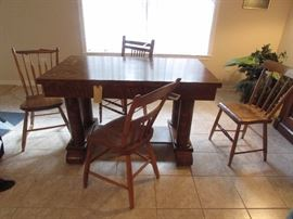 Tiger oak or 1/4 sawn Oak library table with drawer and column decor.  Four miscellaneous wooden vintage chairs