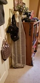 Entertainment center, ironing board, bags and decor