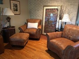 Matching stylish leather chairs and ottoman as well as large framed textiles