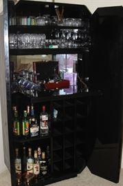 Drop down shelf inside bar. Bottle and stemware storage.