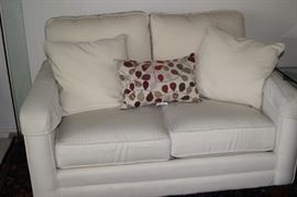 Off white fabric love seat.