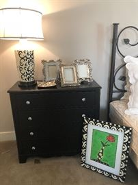 Dresser/nightstand with black and cream lamp, picture frames, framed print - and view of king bed frame!