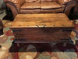 Rustic wooden trunk/coffee table with storage and wrought iron hardware.
