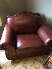 Pleather oversized club chair and ottoman with nail head trim.