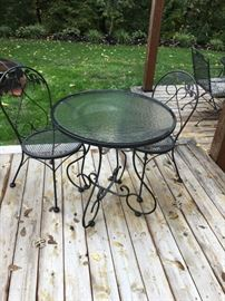 Adorable bistro wrought iron table with glass top and two chairs.