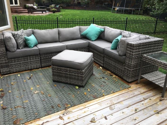 Grey, outdoor wicker L-shaped sofa and ottoman in beautiful condition! Covers (tarps) included.