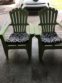 Two green Adirondack chairs.