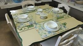 Enamel table with green trim and four white wood chairs