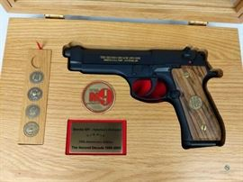 Beretta M9 Commemorative / Defender 1985-2005 2nd Decade, commemorative pistol. Never fired. Black with gold lettering. Solid wood grips. Solid wood display case includes 1 Beretta M9 Challenge coin, and 4/5 Military branch mini-coins (Army. Navy, Marines, Air Force - no Coast Guard). Solid wood/glass display case in excellent condition. 9mm, FFL #273