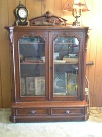 antique glass front cabinet. two lower drawers .