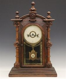 "Welch ""Patti VP"" Shelf Clock - A late 19th century Welch ""Patti VP"" shelf clock.  8-day time and strike movement.  Rosewood case with turned columns and finials on a molded base.  Old finish with minor wear, dial very worn.  Running when cataloged.  19"" high."