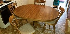 The large leaf comes out to make this into a round pedestal  kitchen table. Comes with 4 sturdy padded chairs.