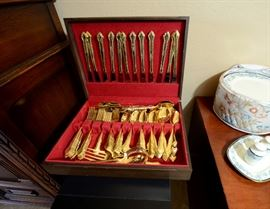 Gold electroplate set of silverware for sale which is siting on top of a wine cooler also for sale.