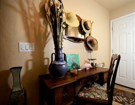 Antique desk and tapestry and wood chair. Antique mirror with hooks to hang hats or other items.