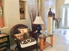 Rattan chair, pretty pillows, glass top side table