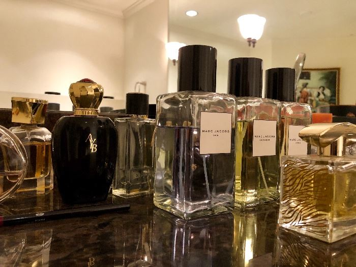 MANY bottles of perfume and other toiletries - many unopened.