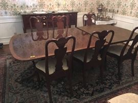 Elegant Duncan Phyfe-style Dining Table with eight matching chairs (pair with arms). Table has double-pedestal base, 2 leaves and pads.
