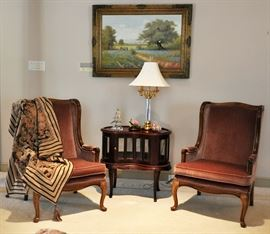 Pair of matching country French wing chairs flanking a very nice reproduction chocolate cabinet with a bluebonnet painting in the background