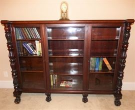 Antique Glass Front Mahogany bookcase with carved paw feet.  This piece came from the Estate of Belmont Dennis