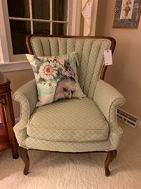 One of a pair of mint upholstered channel back chairs.
