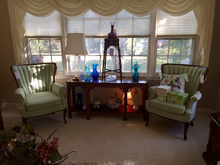 Pair of mint channel back chairs and sofa table with Blenko glassware collection.