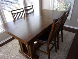 Beautiful wooden kitchen table with 8 chairs, one leaf. Each chair has black, faux leather seat, all in excellent condition.