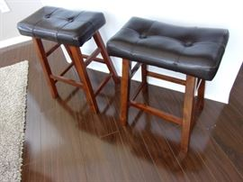 Two faux leather and wood stools.