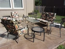 Patio love seat and two armchairs, metal with like-new floral cushions. Two wrought iron patio armchairs. Metal and glass coffee table. Plastic wicker and glass side table. Small Suncast storage bin (with covers for cushioned love seat and armchairs.)