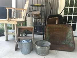 Vintage wheelbarrows, watering cans, pail, metal step ladder, wooden step ladder, porch swing, bird house, and chunky wood table.