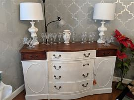 This is a wonderful vintage buffet that is painted in a soft white. The top has been refinished to show the original Mahogany veneer. It has a beautiful waxed finish. The two side drawers are the original finish to add style and maintain some of its great history. This is a very nice clean piece with its original key.