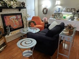 Dark navy blue microfiber love seat and orange chair. Silver glass top tables with a great design.