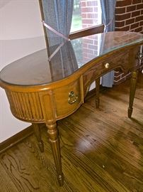 Antique writing desk, kidney shaped with protective glass.