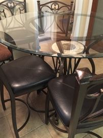 Glass high pub table with four upholstered chairs