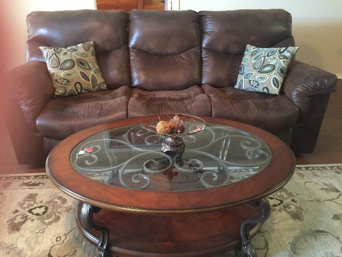 Leather recliner sofa and glass and wood coffee table with metal accents