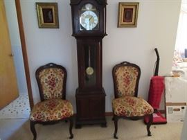 Randolf tall case clock,   flanked by walnut upholstered chairs. Above the chairs are two paintings.