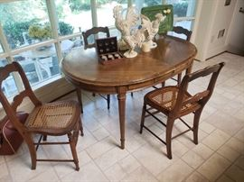French style oval table with four caned-bottom chairs
