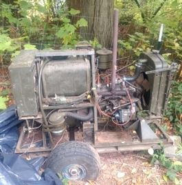 Us military generator from the Korean War era: Flat head, 4 cylinder gas engine with airplane tires, and gas can.