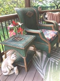 Two-tone wicker high-back armchair with side table; there is also a love-seat and another armchair in the same style. Mother cat and kitten are cement sculpture with glass eyes. Painted flower metal sculpture.