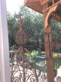 Numerous pieces of metal yard art, including hanging cross sconce and tall obelisk