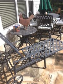 Black metal patio set includes a pair of chaise lounges, pair of small round tables, and a rectangular table with six swivel armchairs. Also a green market umbrella with metal stand. Whimsical metal rooster potted plant holder