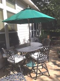 Photo of black metal rectangular table with six swivel armchairs, market umbrella and metal stand.