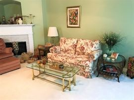 Floral loveseat, Brass and Glass Coffee Table,  Rattan and Glass Table