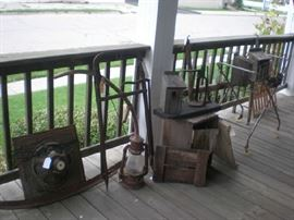 Old speaker, scythe, hay hook, lantern, bird house, bottle capper, wire laundry basket on stand.