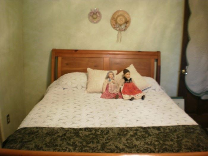 Queen size sleigh bed.  Antique dolls in Eastern Europe dress.